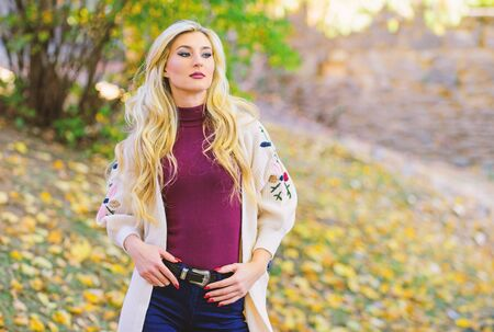 How repair bleached hair fast and safely. Autumn hair care is important so as to avoid dry frizzy hair. Girl fashionable blonde walk in autumn park. Long hair care concept. Cold blonde concept