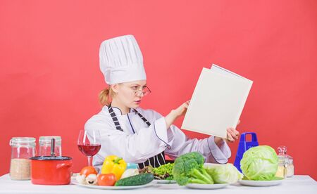 Woman chef cooking healthy food. Girl read book top best culinary recipes. Culinary school concept. Female in hat and apron knows everything about culinary arts. Traditional cuisine. Culinary expert