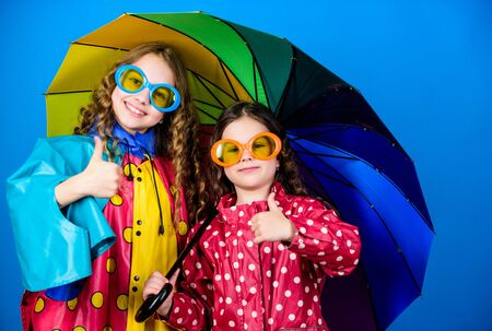 cheerful hipster children, sisterhood. rain protection. Rainbow. happy small girls with colorful umbrella. family bonds. Small girls in raincoat. autumn fashion. Autumn snuggles 版權商用圖片