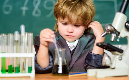 Science concept. Gifted child and wunderkind. Kid study chemistry school. School education. Explore biological molecules. Toddler genius baby. Boy near microscope and test tubes in school classroom