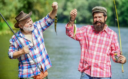 Family let you be who you are. summer weekend. mature men fisher. two fisherman with fishing rods. hobby and sport activity. Trout bait. father and son fishing. male friendship. family bonding