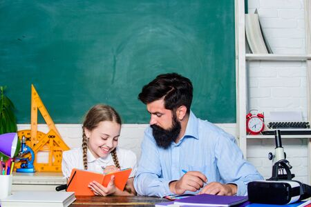 Capricious girl. daughter study with father. Teachers day. education child development. back to school. knowledge day. Home schooling. bearded man teacher with small girl in classroom Фото со стока