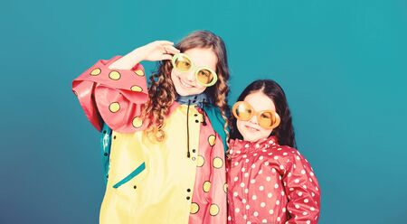 Small girls in raincoat and glasses. happy small girls in colorful rain coat. rain protection. Rainbow. autumn fashion. cheerful hipster children, sisterhood. having fun. Best way to spend vacations