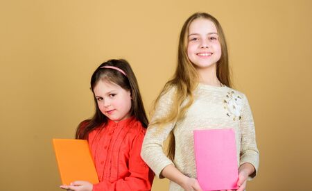 Opening doors through literacy. Kids girls with books or notepads. Education and kids literature. Favorite fairytale. Sisters pick books to read together. Adorable girls love books. Secret diary