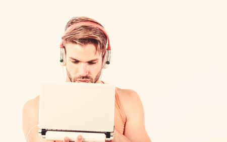 Searching for favorite music. muscular man listen audio. man in earphones isolated on white. e book. unshaven man listening audio book. usinf laptop and headset. copy space Zdjęcie Seryjne