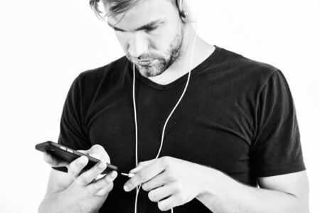 man using wireless blue tooth headset. relax playlist. muscular man listen music from playlist. man relax in earphones isolated on white. unshaven man relax with favorite song