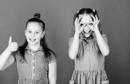 Childhood is a fun time. Happy little girls having fun together. Small children gesturing and making funny faces for fun. Cute kids smiling while making some fun