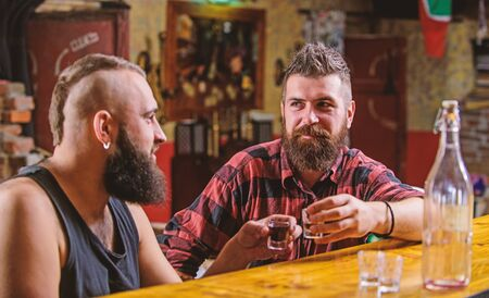 Interesting conversation. Hipster brutal bearded man spend leisure with friend at bar counter. Men relaxing at bar. Strong alcohol drinks. Friday relaxation in bar. Friends relaxing in bar or pub