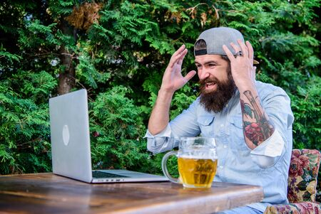 Beer helps him relax after hard day. Brutal man leisure with beer and laptop. Finally friday. Hipster relax sit terrace with beer. Bearded hipster freelancer enjoy end of working day with beer mug