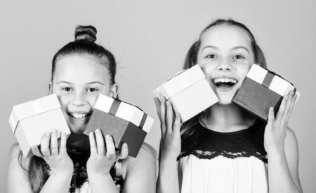 children. Little sisters with gift. Surprise. Family sisterhood congratulation. Happy birthday. Holiday celebration. Boxing day. Christmas shopping. Small girls with present box