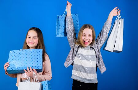 Small girls with shopping bags. Sisterhood family. savings on purchases. Kid fashion. Blue backdrop. Sales discounts. Happy children. Little girl sisters. Small girls with pack. Small girls in mall