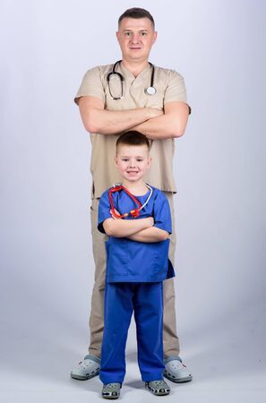 Father doctor with stethoscope and little son physician uniform. Medicine and health care. Future profession. Want to be doctor as dad. Cute kid play doctor game. Family doctor. Pediatrician concept
