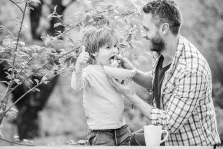 Family enjoy homemade meal. Father son eat food and have fun. Little boy and dad eating. Nutrition for kids and adults. Healthy nutrition concept. Feeding baby. Menu for children. Nutrition habits Stockfoto