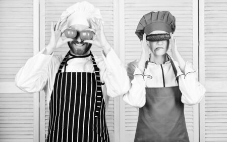 Couple play with ingredients for vegan dish. Cooking vegan meal. Cooking together is fun. Menu for our family. Go vegan. Organic nutrition. Vegan family. Man and woman chef hold vegetables having fun Stockfoto