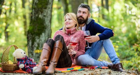 Enjoying their perfect date. Happy loving couple relaxing in park together. Romantic picnic with wine in forest. Couple in love celebrate anniversary picnic date. Couple cuddling drinking wine