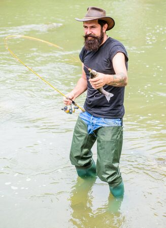Brutal man wear rubber boots stand in river water. Fisher weekend activity. Fisher with fishing equipment. Fish on hook. Leisure in wild nature. Fun of fishing is catching. Fishing masculine hobby Zdjęcie Seryjne