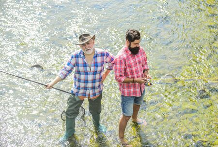 Men bearded fishermen. Weekends made for fishing. Active sunny day. Fishermen fishing equipment. Hobby sport activity. Fishermen friends stand in river. Fish normally caught in wild. Summer leisure Zdjęcie Seryjne