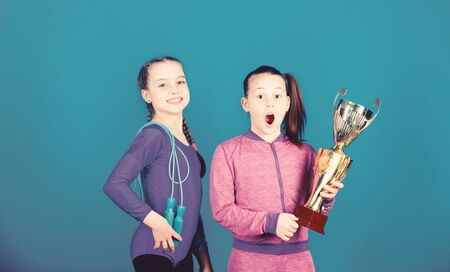 Deserved award. Sport achievement. Girls athletic kids celebrate victory. Athletic girls with golden goblet. Win championship. Our team first place. Children gymnasts athletic kids happy champions