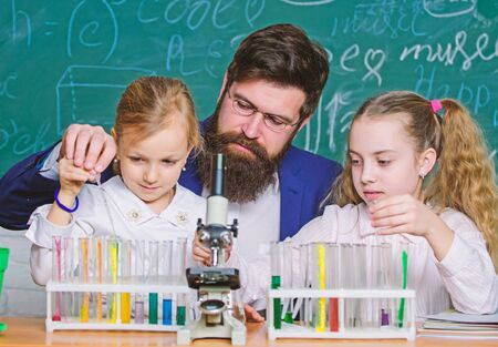 Man bearded teacher work with microscope and test tubes in biology classroom. How to interest children study. Explaining biology to children. Fascinating biology lesson. School teacher of biology