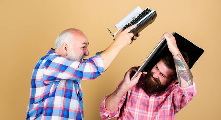 confrontation. technology battle. Modern life. youth vs old age. business approach. father and son. family generation. two bearded men. Vintage typewriter. retro typewriter vs laptop. New technology Stock Photo