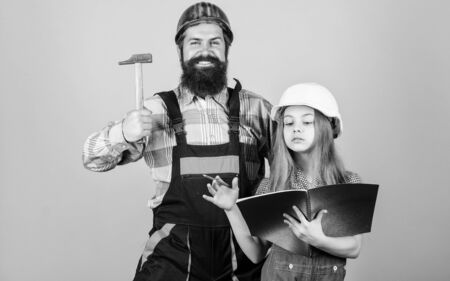 Home improvement activity. Kid girl planning renovation. Child renovation room. Family remodeling house. Little fathers helper. Father bearded man and daughter hard hat helmet uniform renovating home Фото со стока - 129257503