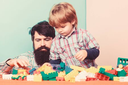 Child development and upbringing. Father and son have fun. Importance of playing together. Bearded hipster and boy play together. Dad and child build plastic blocks. Child care concept. Happy family