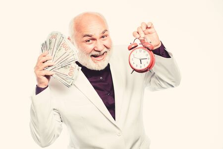 time management. business success. retirement. time and age. Timekeeping. mature bearded man with alarm clock. mature man with beard hold money. clock show time. time is money. making money