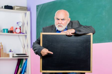 look here. information is here. place for copy space. Mature teacher man hold chalk board. exam and graduation results. senior man teacher with empty blackboard. back to school. Education concept Stock Photo