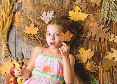 Tips for turning autumn into best season. Autumn coziness is just around. Coziest things about fall. Kid cute girl relax wooden background autumn attributes top view. Child long hair with dry leaves