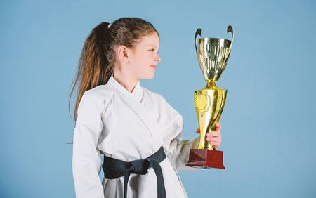 Girl little child in white kimono with belt. Karate fighter child. Karate sport concept. Self defence skills. Karate gives feeling of confidence. Celebrate achievement. Strong and confident kid