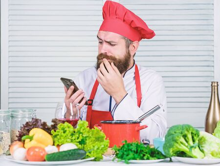 Man chef searching internet recipe cooking food. Chef smartphone watch culinary show. Culinary school. Hipster in hat and apron learning how cook online. Culinary education online. Elearning concept 写真素材