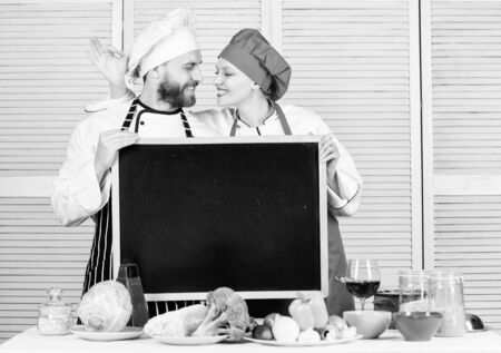 Learning with culinary experts. Chef and cook helper gesturing ok at board in cooking school. Couple of man and woman teaching cooking class. Master cook and prep cook giving master class, copy space Фото со стока