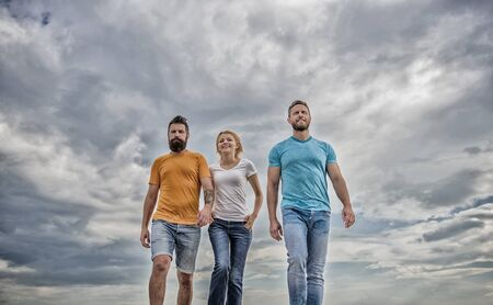United threesome true friends. Men and woman walks dramatic cloudy sky background. True friendship grow with destiny obstacles. United group purposefully moves forward. Friendship tested for years