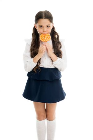 Healthy nutrition diet. Girl pupil school uniform like sweets lollipop candy white background. Sweets reward for study. Rewarding herself with sweets. Food addictions. Girl kid eat sweet lollipop Stock Photo