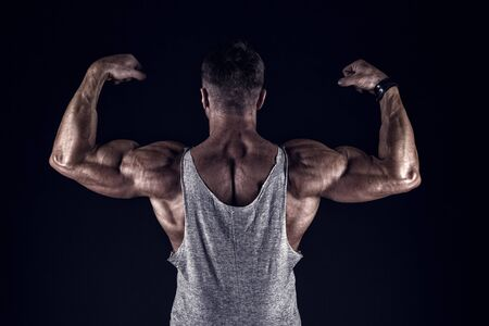 bodybuilding and sport. strength and shape concept. Sport and fitness. Bodybuilder showing muscles, biceps and triceps. flexing arms with fists. bodybuilding. bodybuilder show his muscles. body care