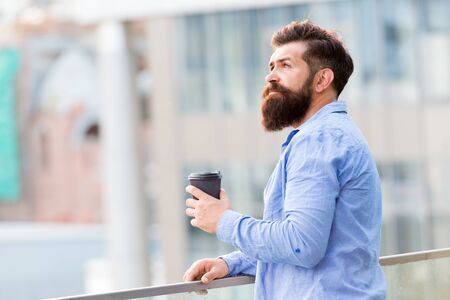 Bearded man relax. brutal hipster with coffee cup. energy charge. Male barber care. copy space. Time zone. thoughtful man drink take away coffee outdoor. morning coffee. Mature hipster with beard Фото со стока