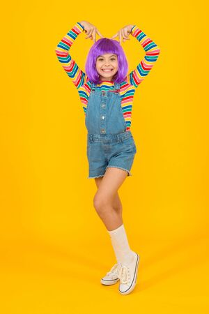 Cosplay outfit. Otaku girl in wig smiling on yellow background. Cosplay character concept. Culture hobby and entertainment. Happy childhood. Anime fan. Cosplay kids party. Child cute cosplayer
