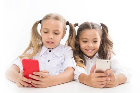 Smart pupils. Little pupils texting message during class isolated on white. Cute lyceum pupils diving deep into smartphone lessons. Small pupils using mobile phones in classroom Stock fotó