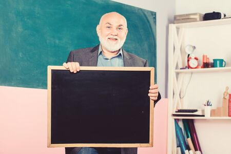 back to school. Education concept. place for copy space. Mature teacher man hold chalk board. information is here. exam and graduation results. senior man teacher with empty blackboard. Modern school Banco de Imagens