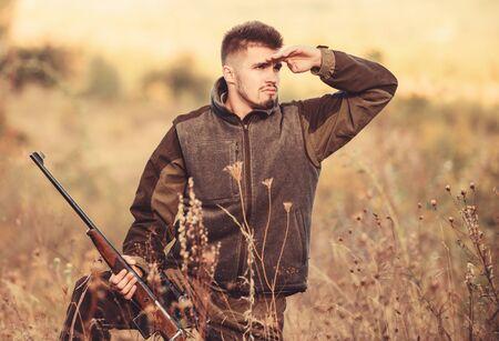 Polowanie to brutalne męskie hobby. Sezony łowieckie i łowieckie. Człowiek brutalne nieogolony gajowy natura tło. Pozwolenie na polowanie. Brodaty poważny myśliwy spędza czas wolny na polowaniu. Hunter trzymaj karabin Zdjęcie Seryjne