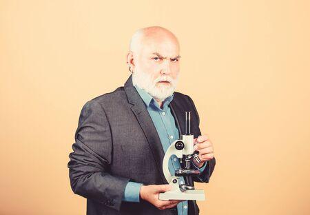 Progetti di dottorato in biologia molecolare. Abito formale uomo maturo con microscopio. Professore docente universitario. Scienziato microbiologia. Lavoro di dottorato e lavoro post-dottorato. Docente esperto di biologia