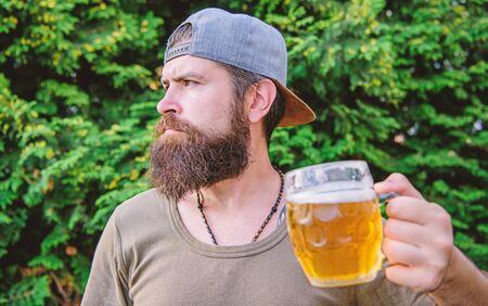 Drinking culture. Hipster holding beer mug. Bearded hipster drinking beer on summer nature. Hipster drinker. Hipster man with craft beer. Brutal man with drinking habits. Drinking only heavy beer