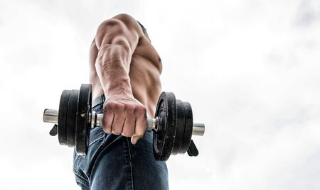 athletic body. Dumbbell gym. Muscular man exercising in morning with barbell. fitness and sport equipment. Healthy lifestyle. athletic man sportsman weightlifting. steroids. copy space