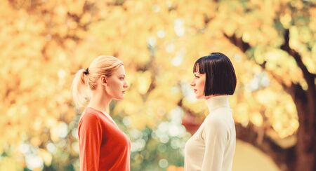 Pretty girls friends sisters. Eye contact. Women looking at each other with attention. Blonde brunette competitors. Female rivalry. Friendship problems rivalry and jealousy. Rivalry and leadership Standard-Bild