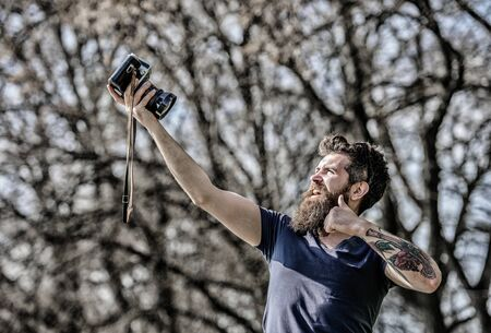 Photographer with beard and mustache. Man with long beard shooting photos. Manual settings. Photographer hold vintage camera. Modern blogger. Content creator. Man bearded hipster photographer Imagens