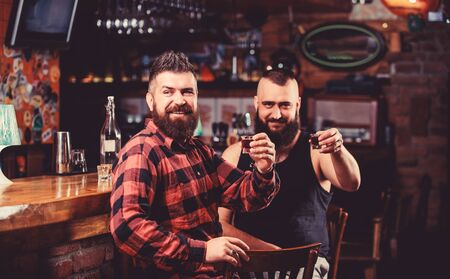 Men relaxing at bar. Friendship and leisure. Friday relaxation in bar. Friends relaxing in pub. Hipster brutal bearded man spend leisure with friend at bar counter. Order drinks at bar counter Фото со стока