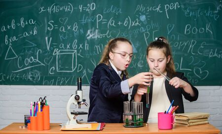 Make studying chemistry interesting. Educational experiment concept. Microscope and test tubes on table. Be careful performing chemical reaction. Basic knowledge of chemistry. Girls study chemistry