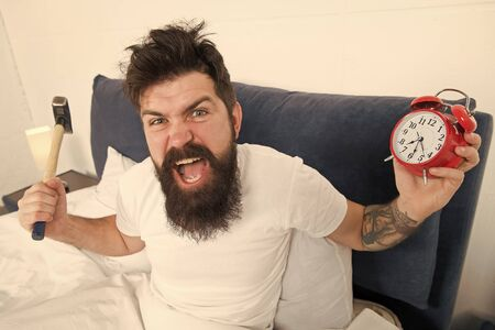 Tips for waking up early. Tips for becoming an early riser. Man bearded hipster sleepy face in bed with alarm clock. Problem with early morning awakening. Get up with alarm clock. Overslept again
