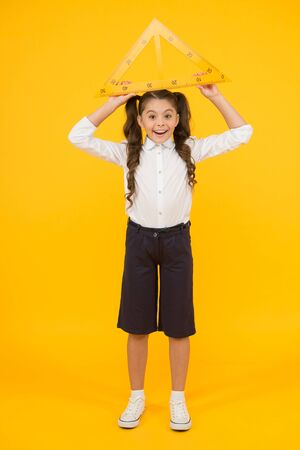 Schoolgirl school uniform hold big ruler geometry school lesson. Kid cute school student study mathematics. Triangle right angle. Knowledge day. Math stem architecture faculty. Measuring equipment
