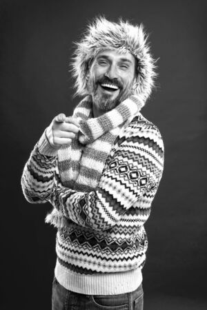 Laughing out loud. Bearded man accessorizing sweater with hat and scarf. A winter ensemble protects him from cold. Winter wardrobe for man. Mature fashion model in cold weather style, vintage filter